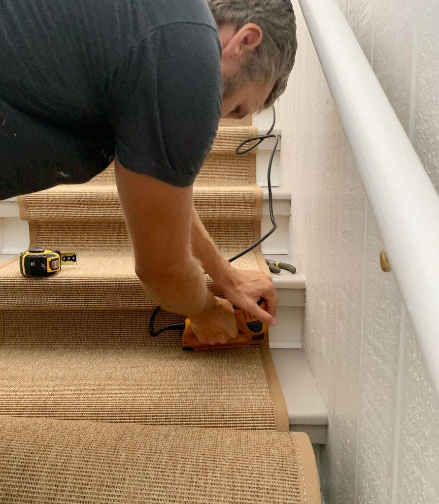 Джон использует электрический степлер для забивания скобы в ступеньку. Нижний угол лестницы для фиксации сизалевой дорожки