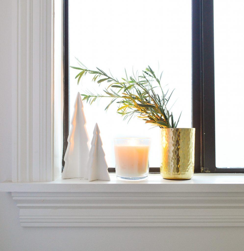 Белые керамические деревья со свечой и золотой вазой на подоконнике в ванной