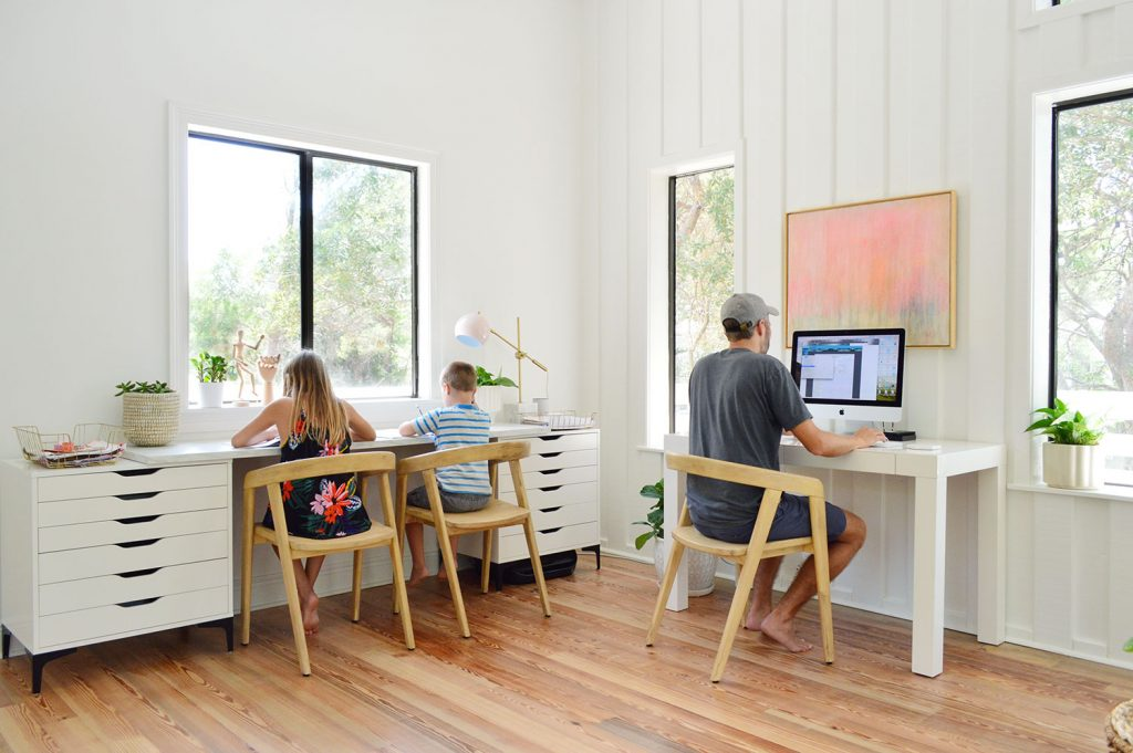 Дети, работающие за столом для рисования с Джоном за офисным столом