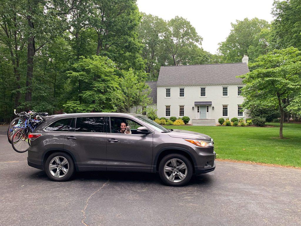 Автомобиль Toyota Highlander припаркован перед домом из белого кирпича