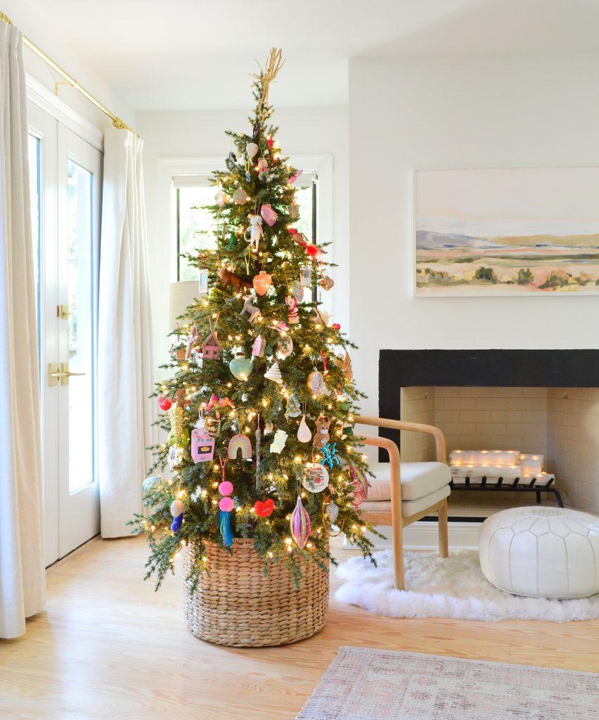 Плетеная корзина у основания рождественской елки с красочными орнаментами