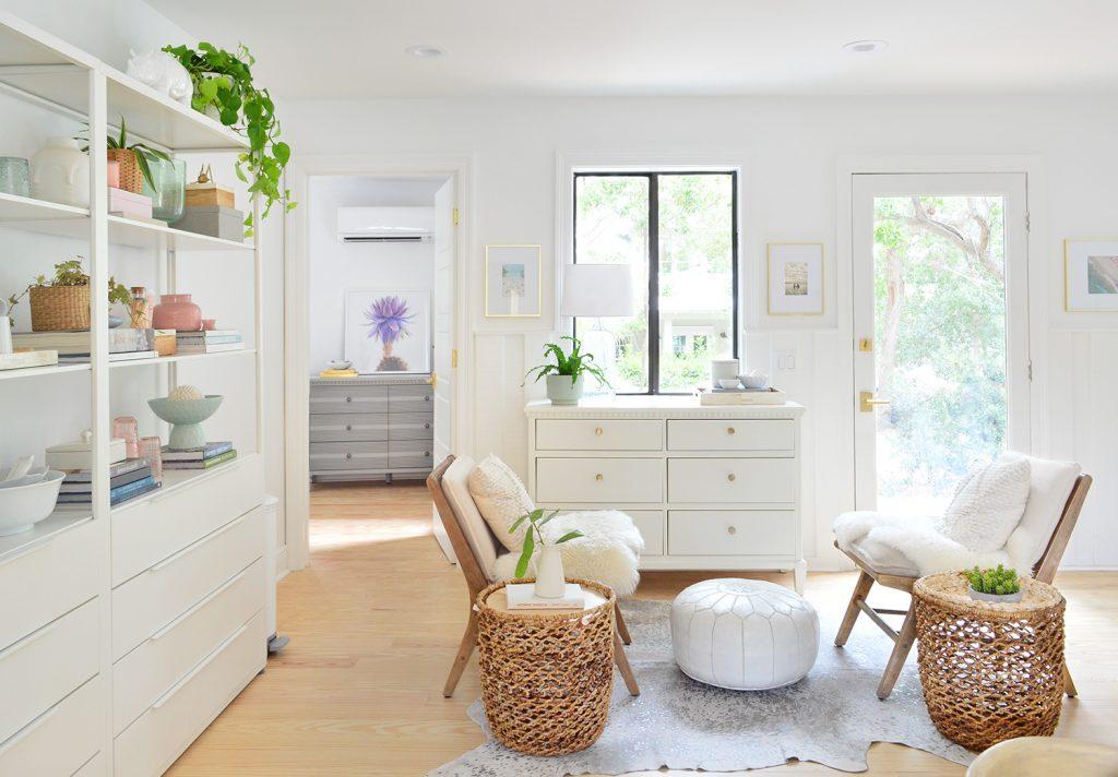 Гостиный уголок в белой кухне со стульями и открытыми стеллажами