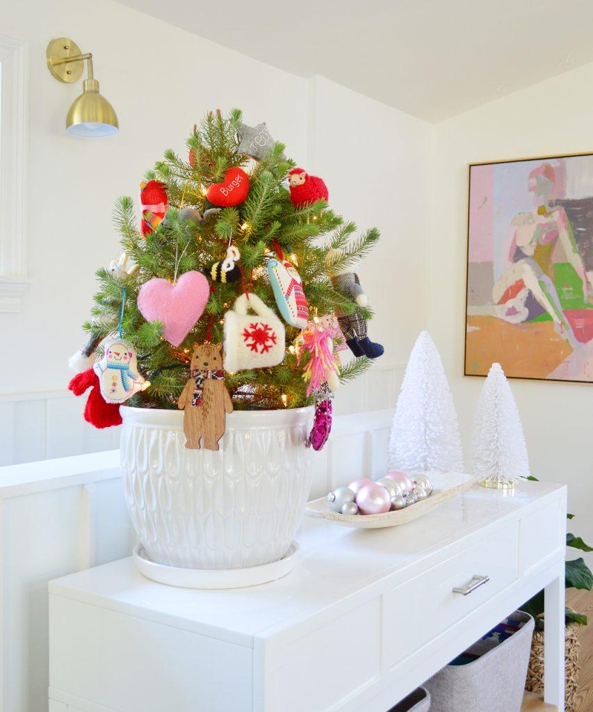 Маленькое настольное дерево в белом горшке с разноцветными орнаментами