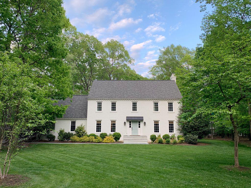 Белый кирпичный дом с большим травяным двором