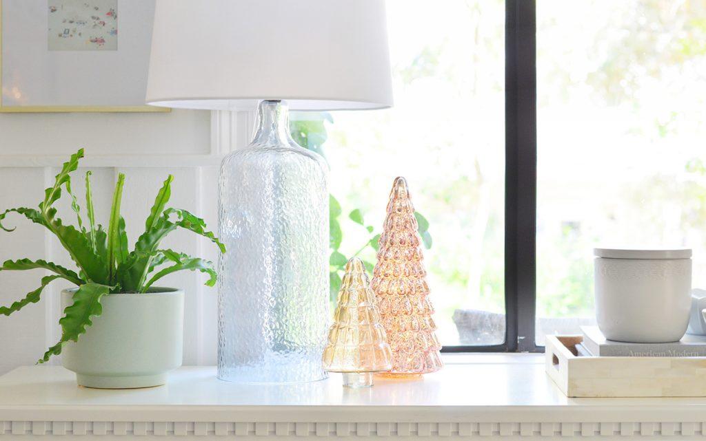 Стеклянные рождественские елки на столе у входа