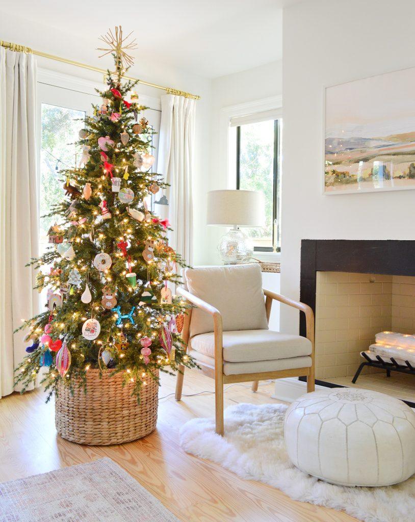 Рождественская елка в плетеной корзине у камина