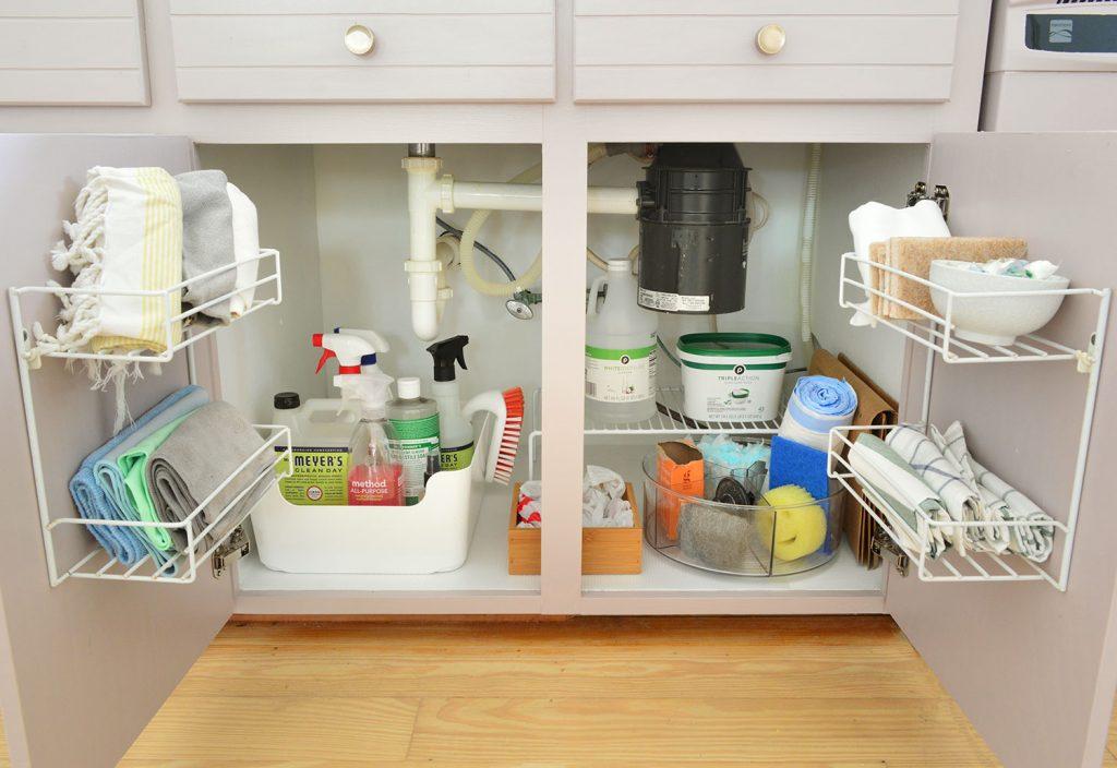Хранилище принадлежностей для чистки под раковиной на кухне с розовато-лиловыми шкафчиками
