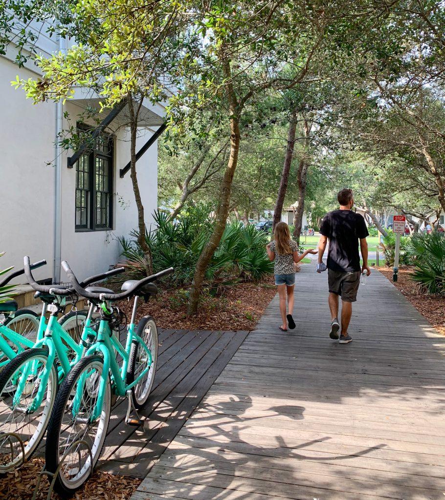 Джон и дочь идут по лесистой дорожке рядом с велосипедами