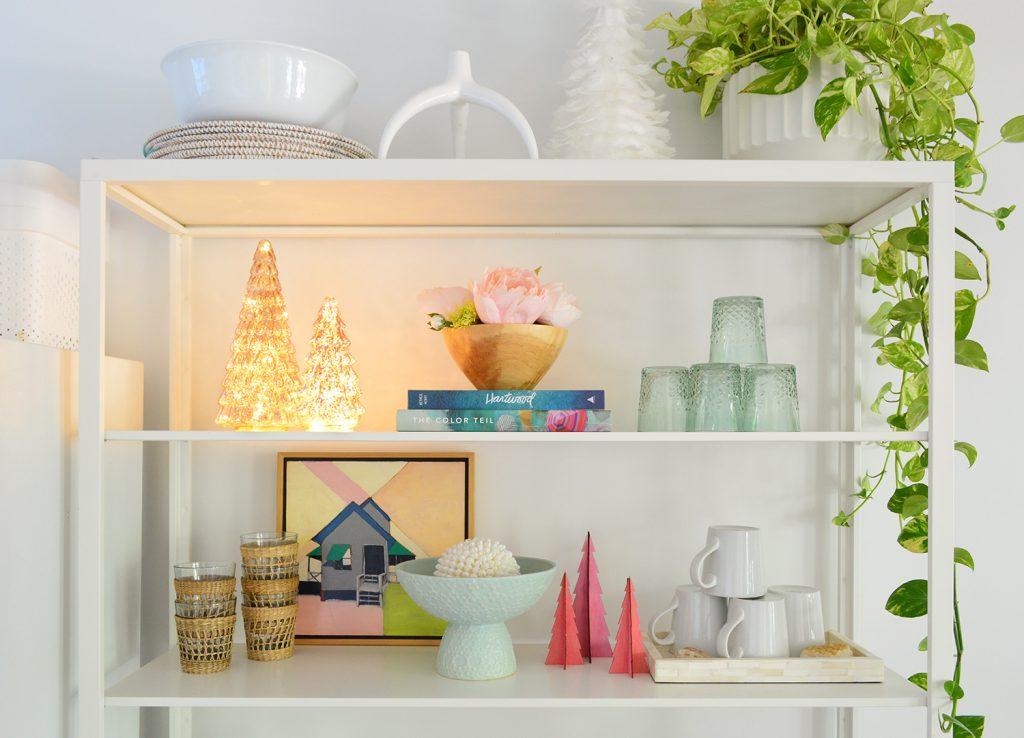 Белые металлические кухонные полки с освещенными яркими рождественскими елками