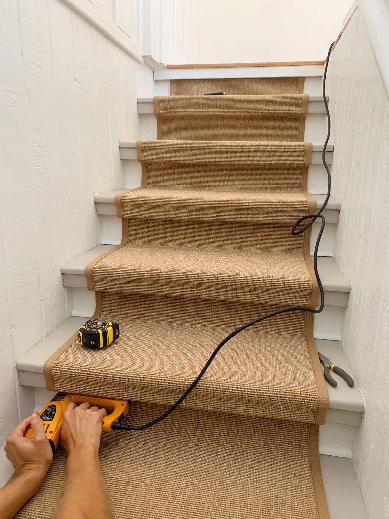 Рука, проталкивающая электрический степлер под ступеньку лестницы, чтобы закрепить сизалевый бегунок