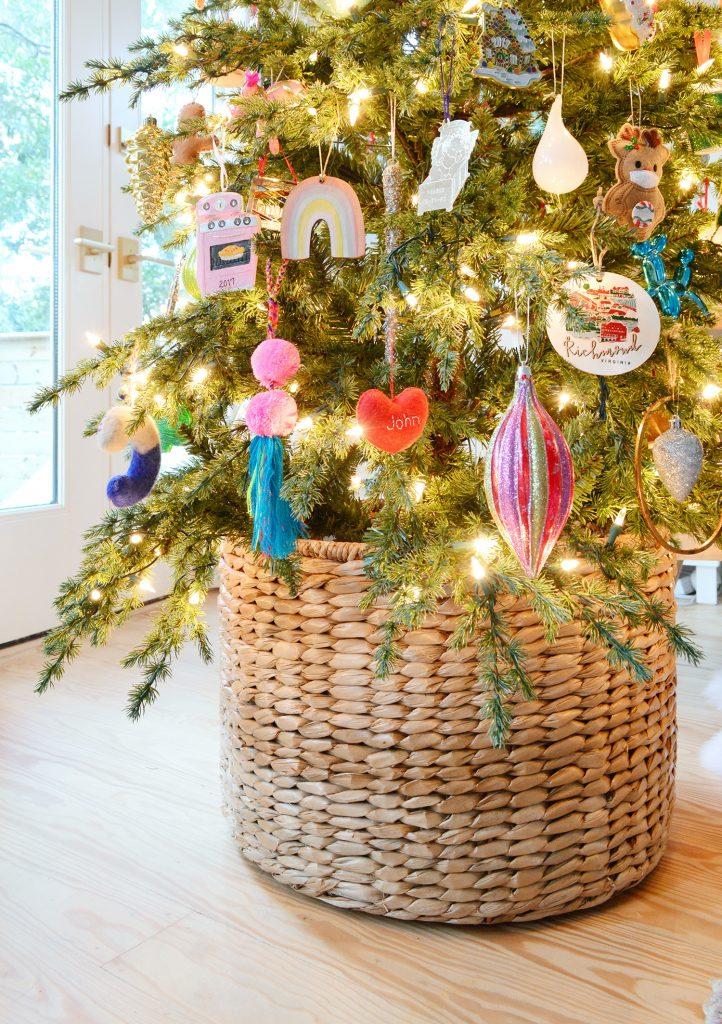 Плетеная корзина у основания рождественской елки с разноцветными орнаментами
