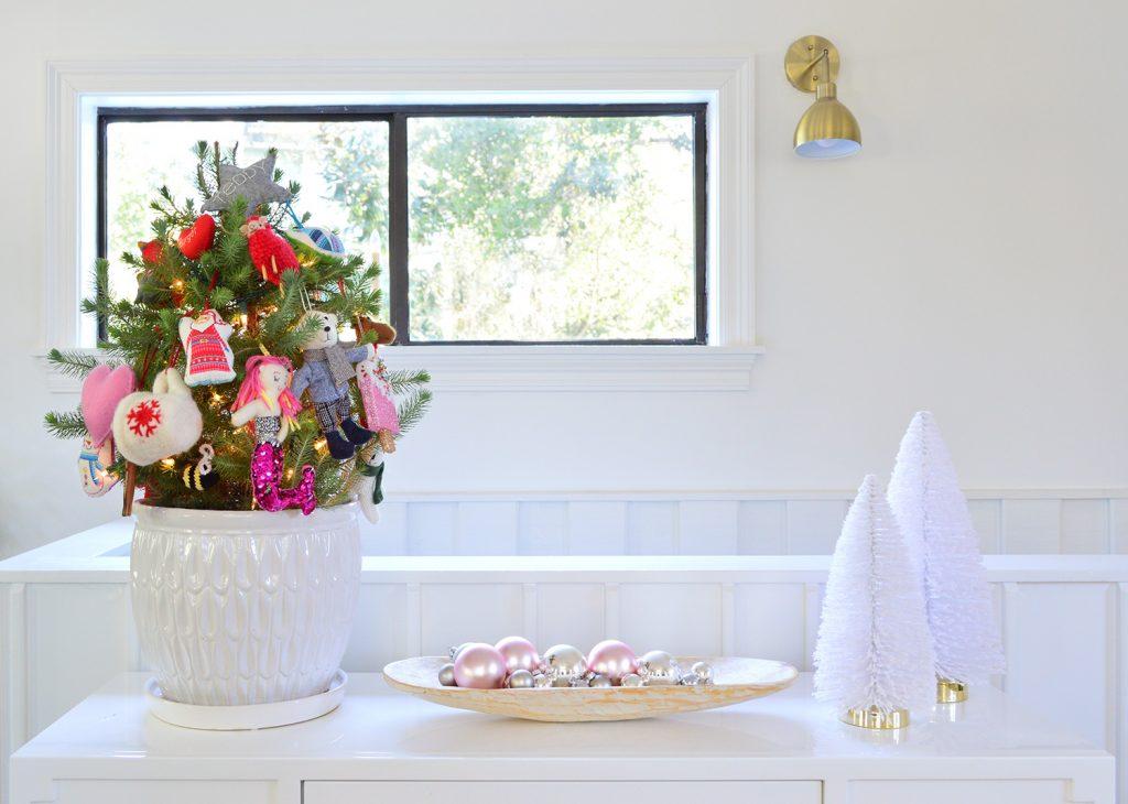 Белая столешница с маленькими деревьями, блестящими орнаментами и деревьями-щетками