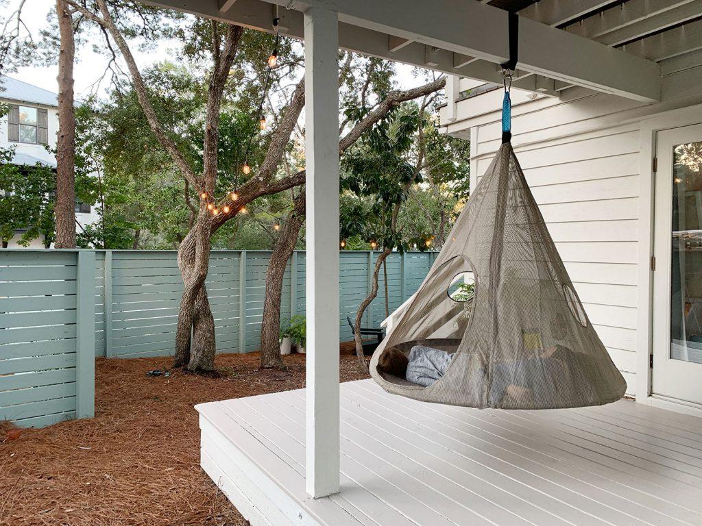 Двое детей лежат в подвесной палатке на крытой веранде