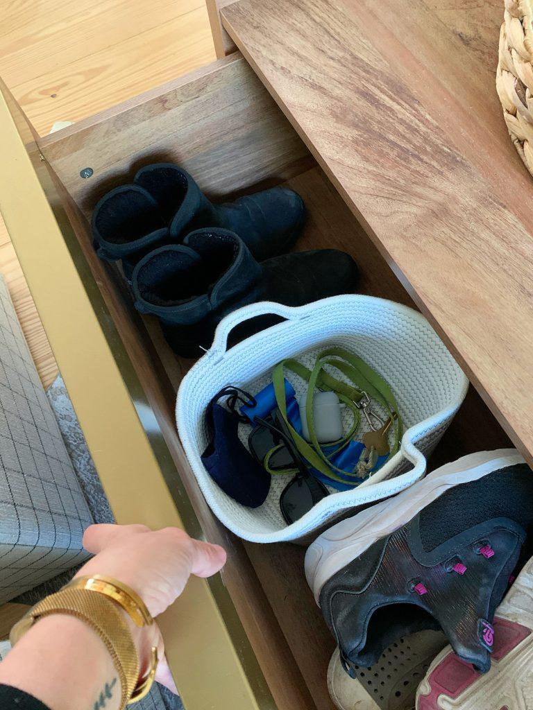 Открытый ящик деревянного журнального столика с ботинками и корзиной с ключами