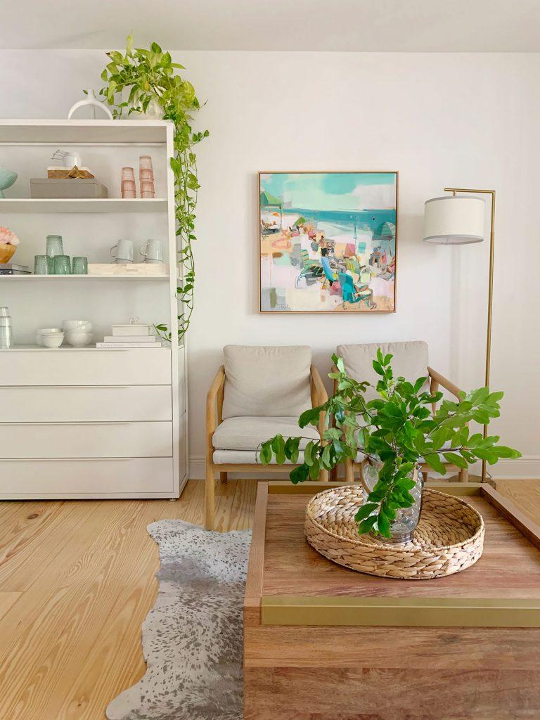 Вид сбоку на гостиную с растениями на журнальном столике и подвешенную к кухонной полке