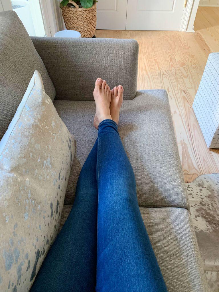 Ноги Шерри раскинуты на сером диванчике