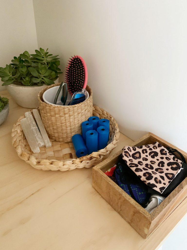 Корзины и урны на полке для белья с аксессуарами для входа, такими как маски, сумки для собак и солнцезащитные очки