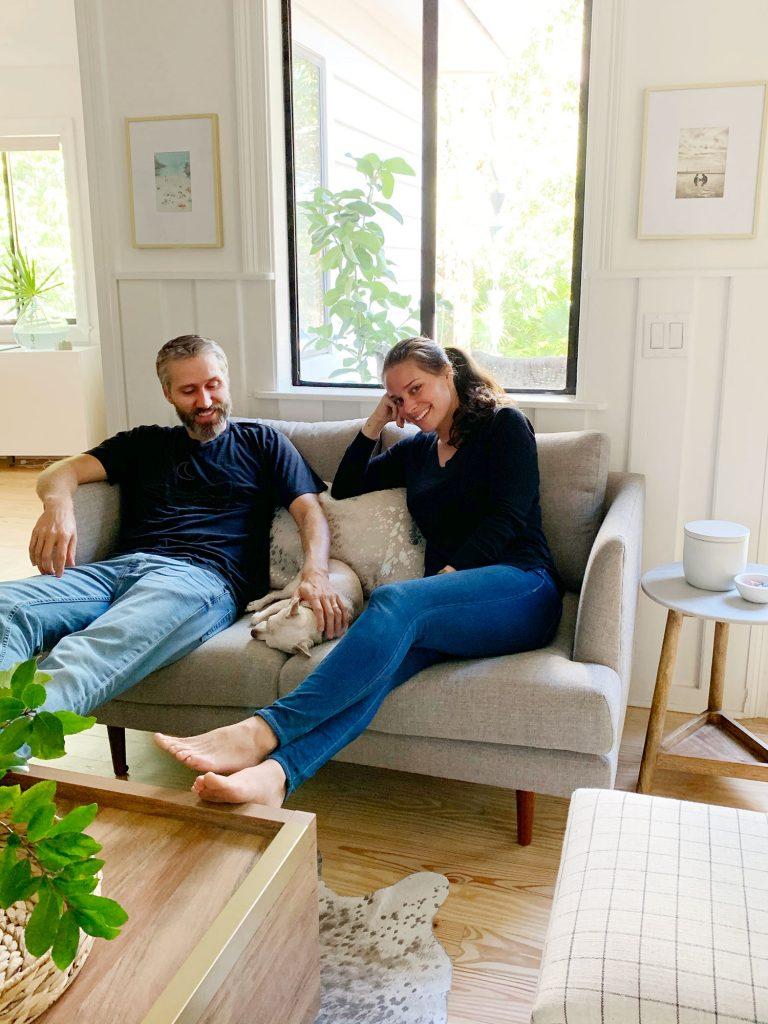 Джон и Шерри сидят вместе с чихуахуа на сером диванчике