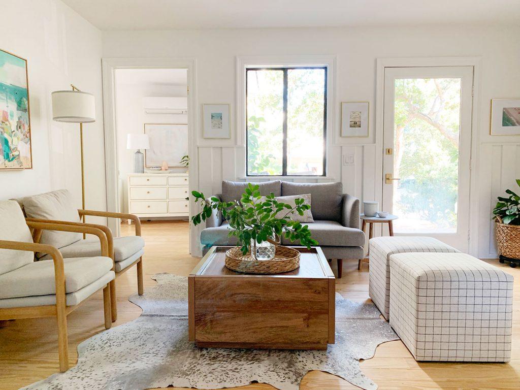 Гостиная, включая деревянный журнальный столик, две клетчатые оттоманки, два кресла и серый диванчик