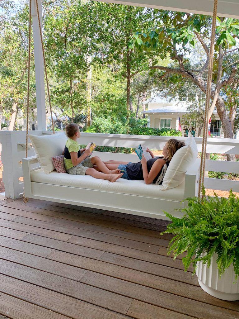 Двое детей читают на обоих концах белых подвесных качелей на кушетке