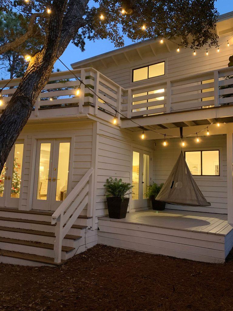 Внешний вид белого дома ночью с подвесными качелями на крытой боковой веранде