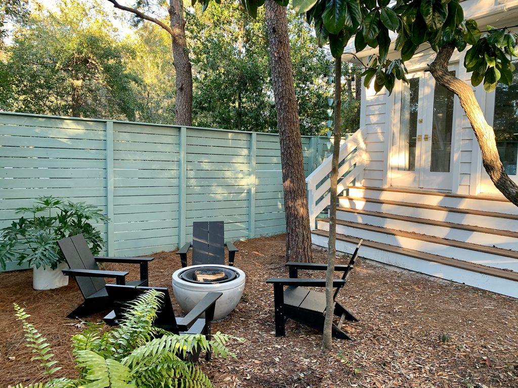 Окрашенный в сине-зеленый цвет горизонтальный забор вокруг бокового двора с длинными ступенями, ведущими в спальню