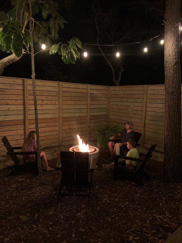 Семья сидит у костра с неокрашенным забором