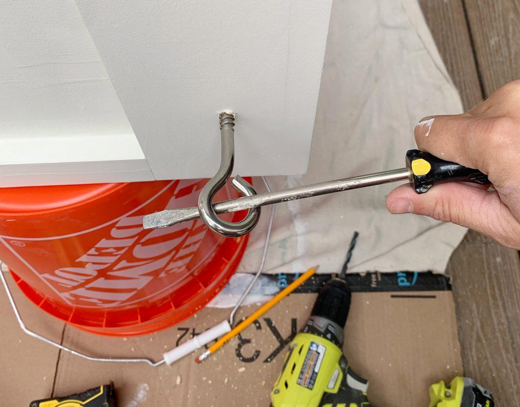 Поворачивание крючка для ушка в подвесной кушетке с помощью длинной отвертки