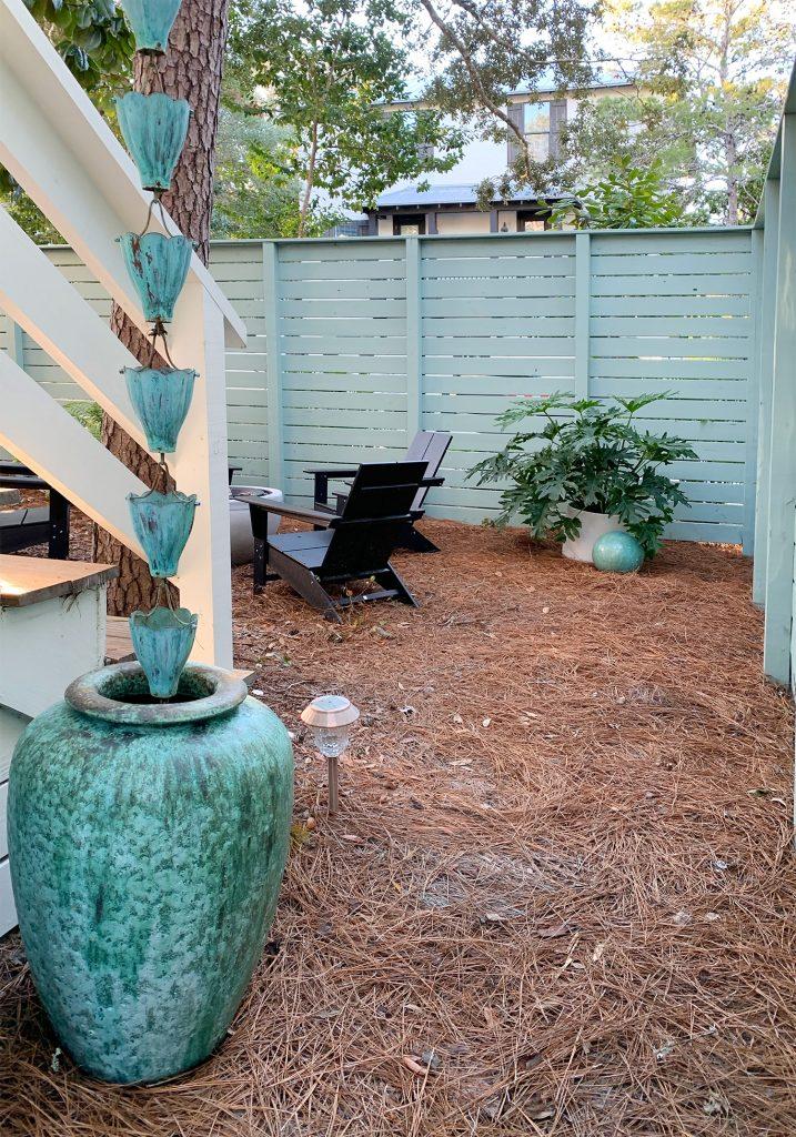 Вид через забор ворот рядом с сине-зеленым горшком и дождевой цепью
