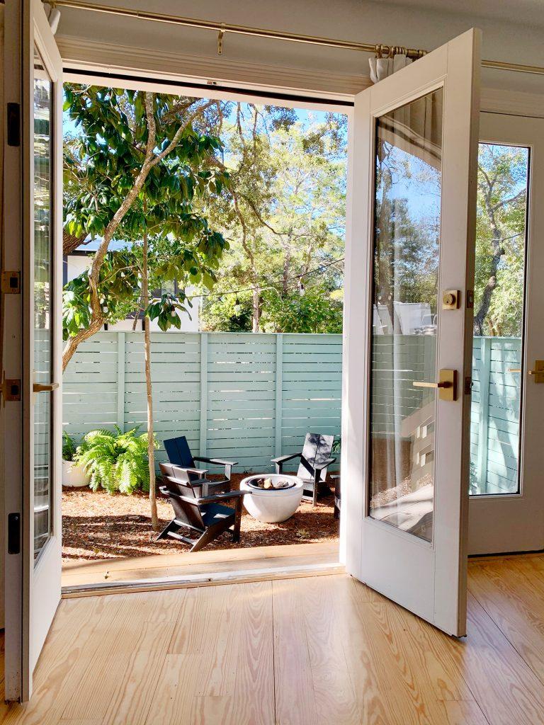 Вид на место для костра через открытые французские двери в спальне