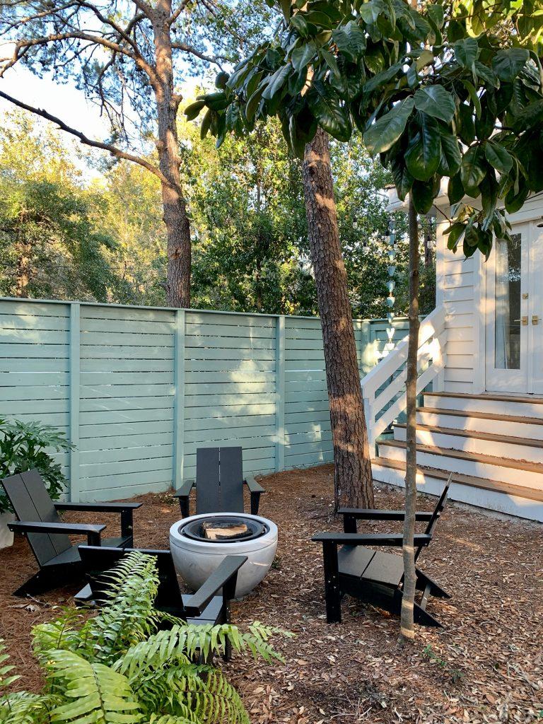 Деревья вокруг огороженного бокового двора с черными стульями из адирондака вокруг костровой ямы