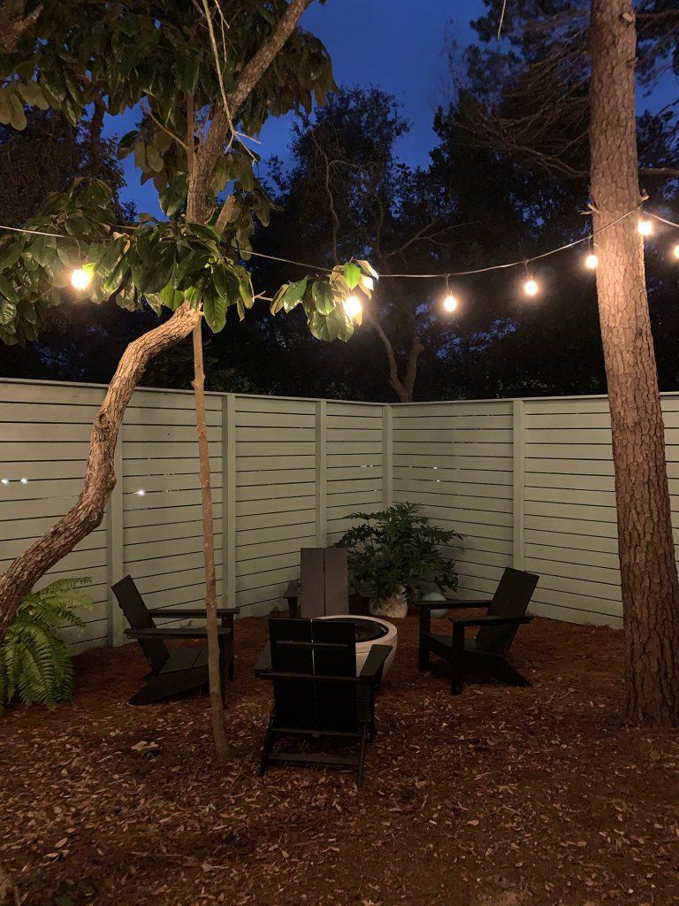 Ночной вид на огороженный боковой двор с черными стульями из адирондака вокруг костровой ямы