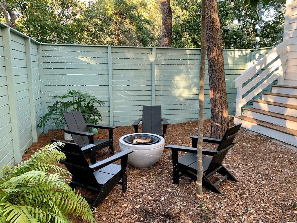 Окрашенный огороженный боковой двор с черными стульями из адирондака вокруг костровой ямы с горшечными растениями