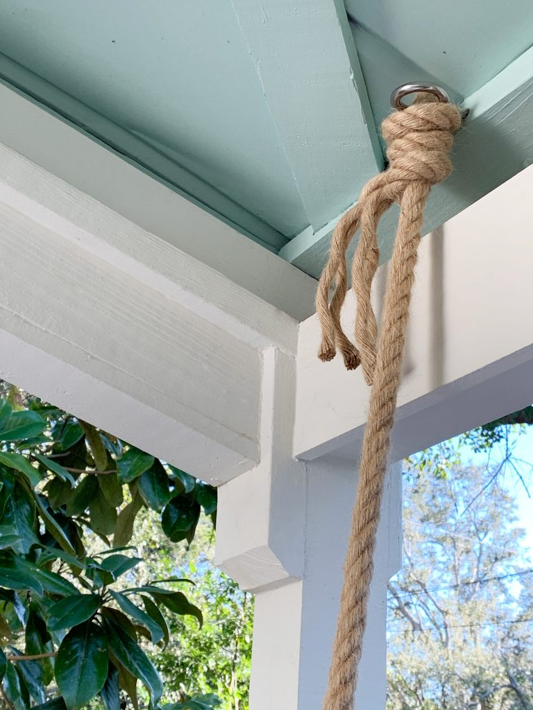 Веревка обвязана вокруг крюка с проушиной на потолке. крытая веранда