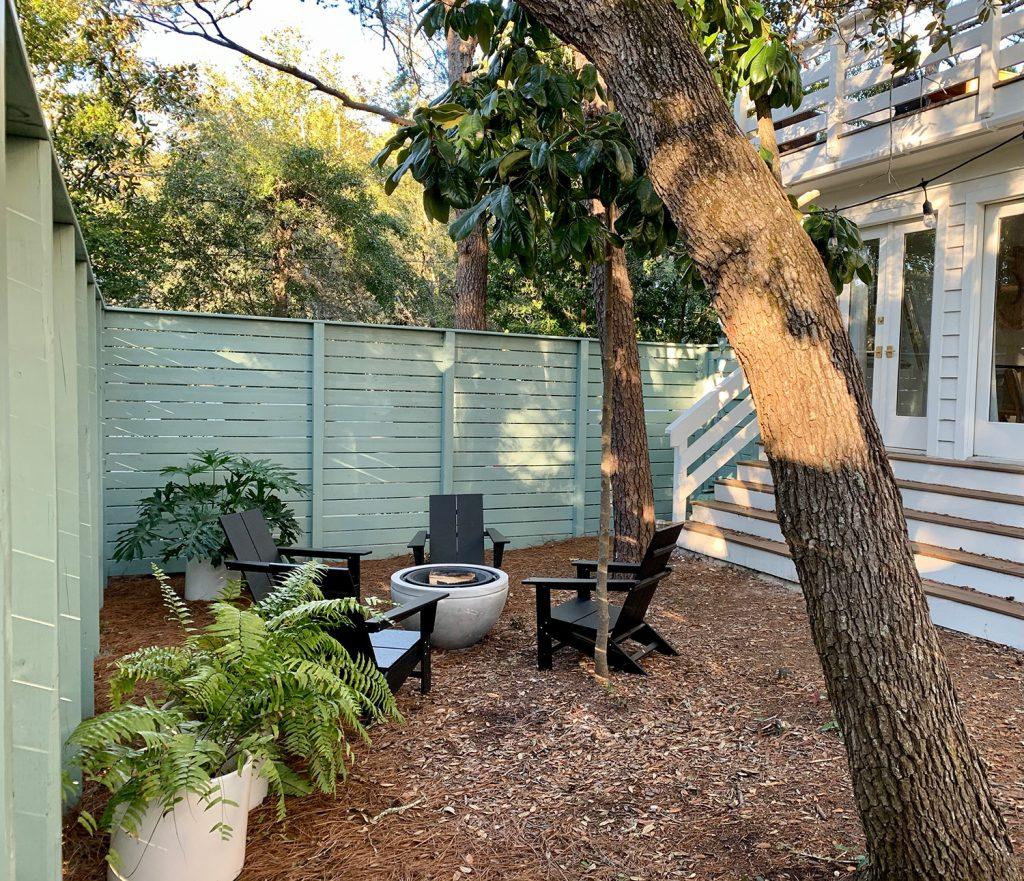 Зеленый огороженный боковой двор с черными стульями из адирондака вокруг костровой ямы