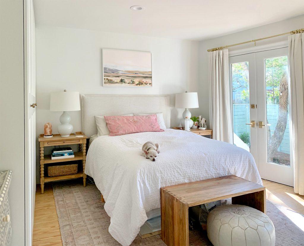 Спальня с розовым ковром и французскими дверями рядом с белой кроватью.