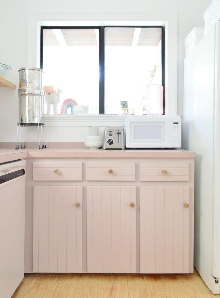 Кухня с розовато-лиловыми шкафами и окном над прилавком
