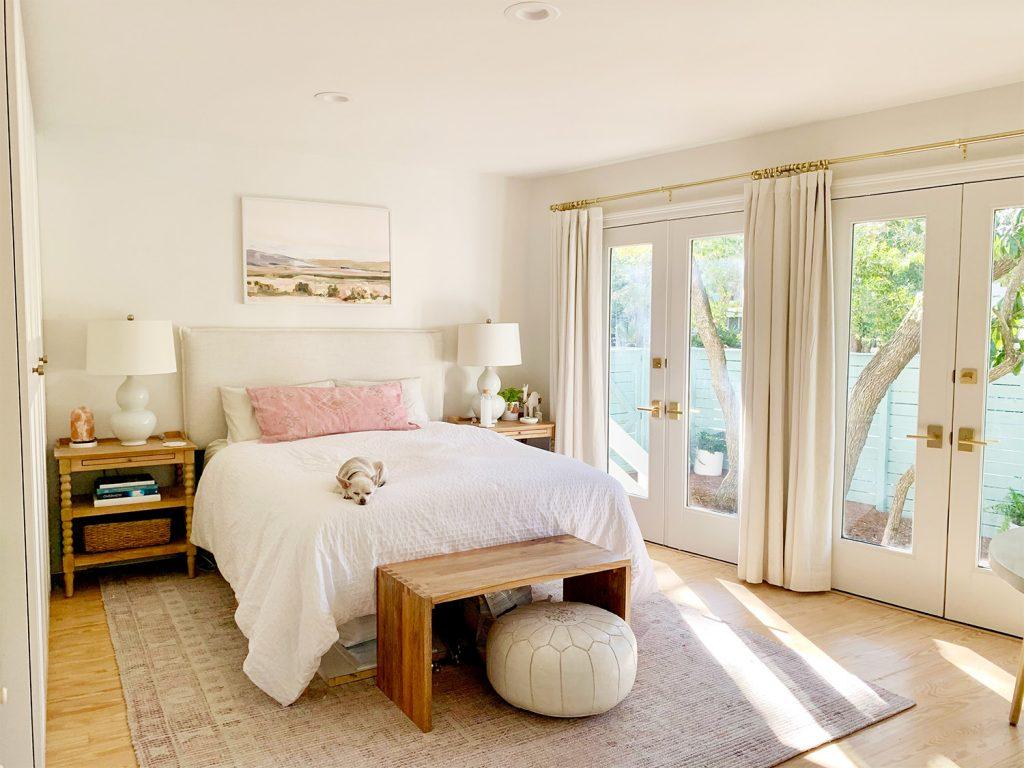 Спальня с розовым ковриком с французскими дверями рядом с белой кроватью