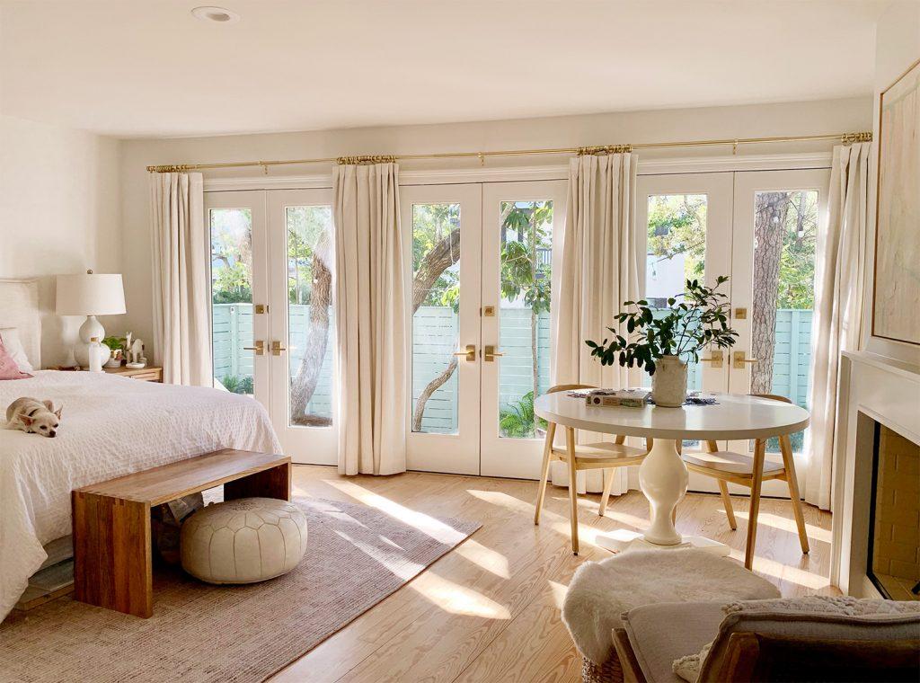 Спальня с тремя французскими дверями с занавесками и солнечным светом входящий в